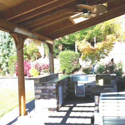 Outdoor kitchen with heaters and ceiling fan in Tigard by Classic Electric