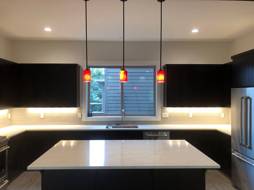 Kitchen remodel with recessed can lights pendant lights and countertop plugs
